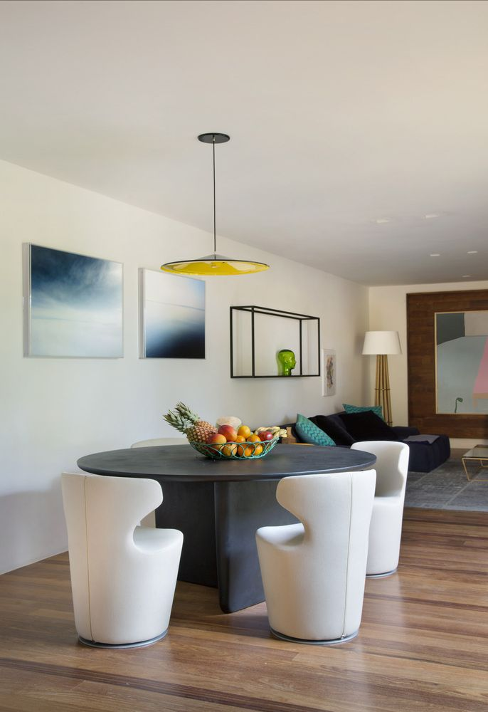 The dining area has a very fresh and serene vibe highlighted by the white accent wall and abstract artwork