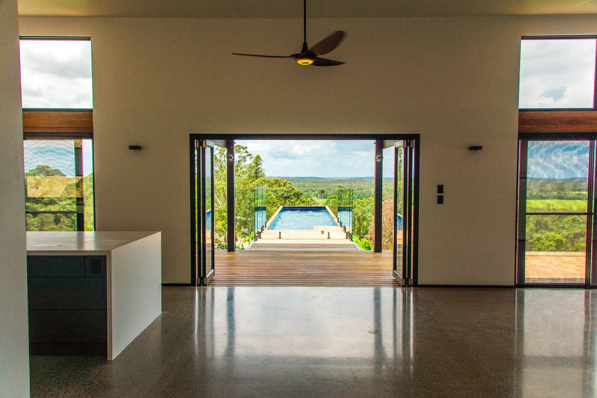 The swimming pool is placed perpendicularly to the wooden deck and the interior living spaces