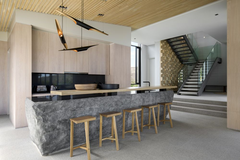 The kitchen, dining space and lounge area form an open plan volume situated at the center of the C-shaped house