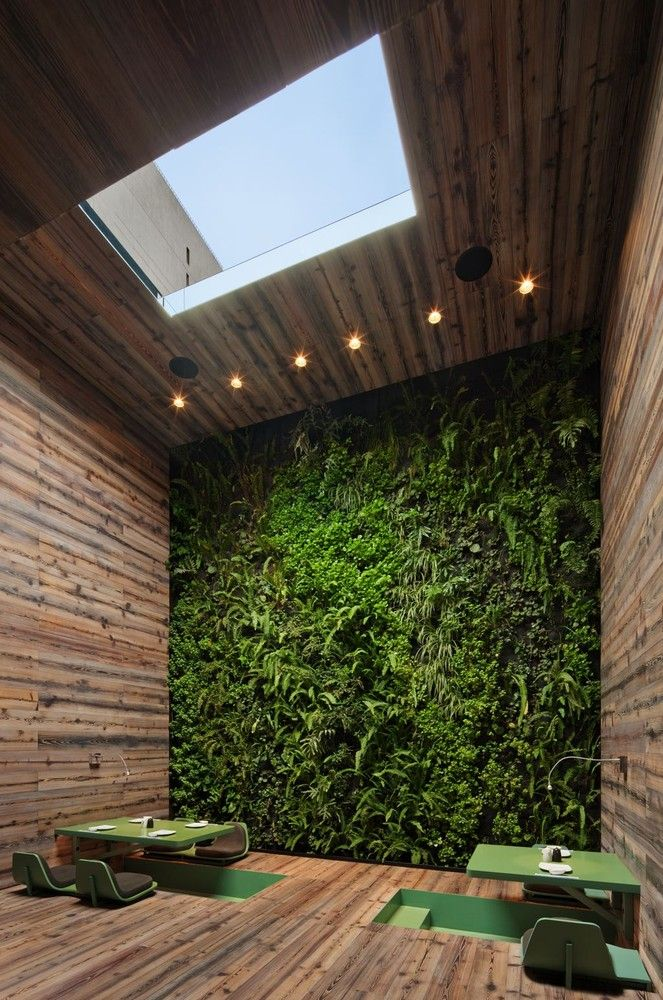 A green wall accents the Tori Tori Restaurant in Mexico City by Rojkind Arquitectos + ESRAWE Studio.