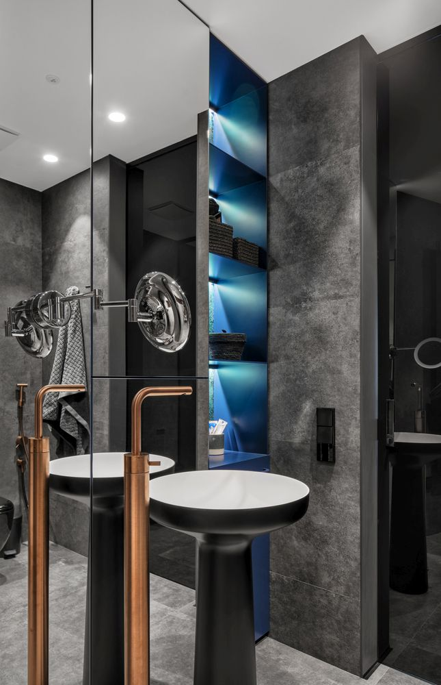 The bathroom's dark color palette is balanced by a blue nook and copper fixtures