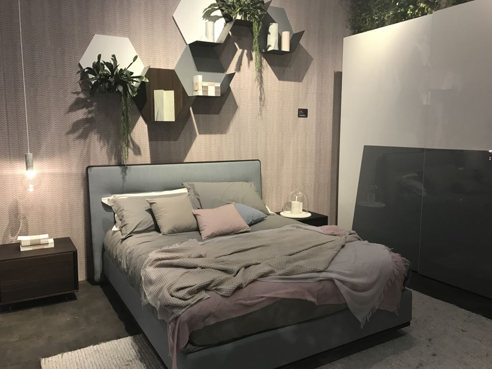 Bedroom with hanging shelves and plants above headboard