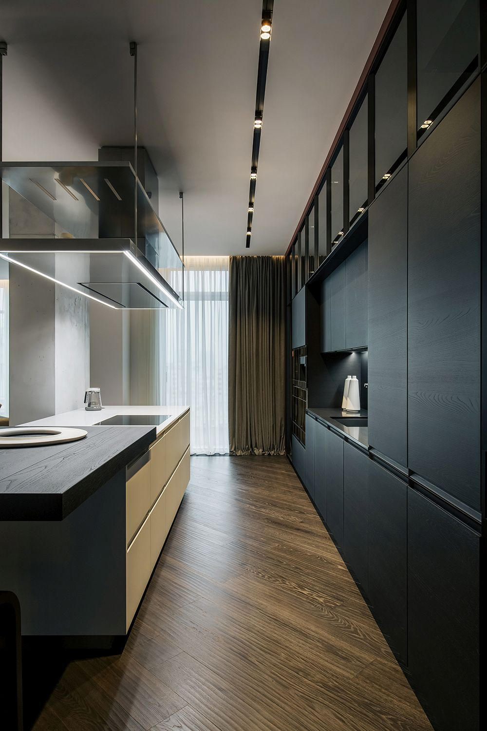 Dark wooden floors throughout the apartment ensure a seamless visual connection between the spaces