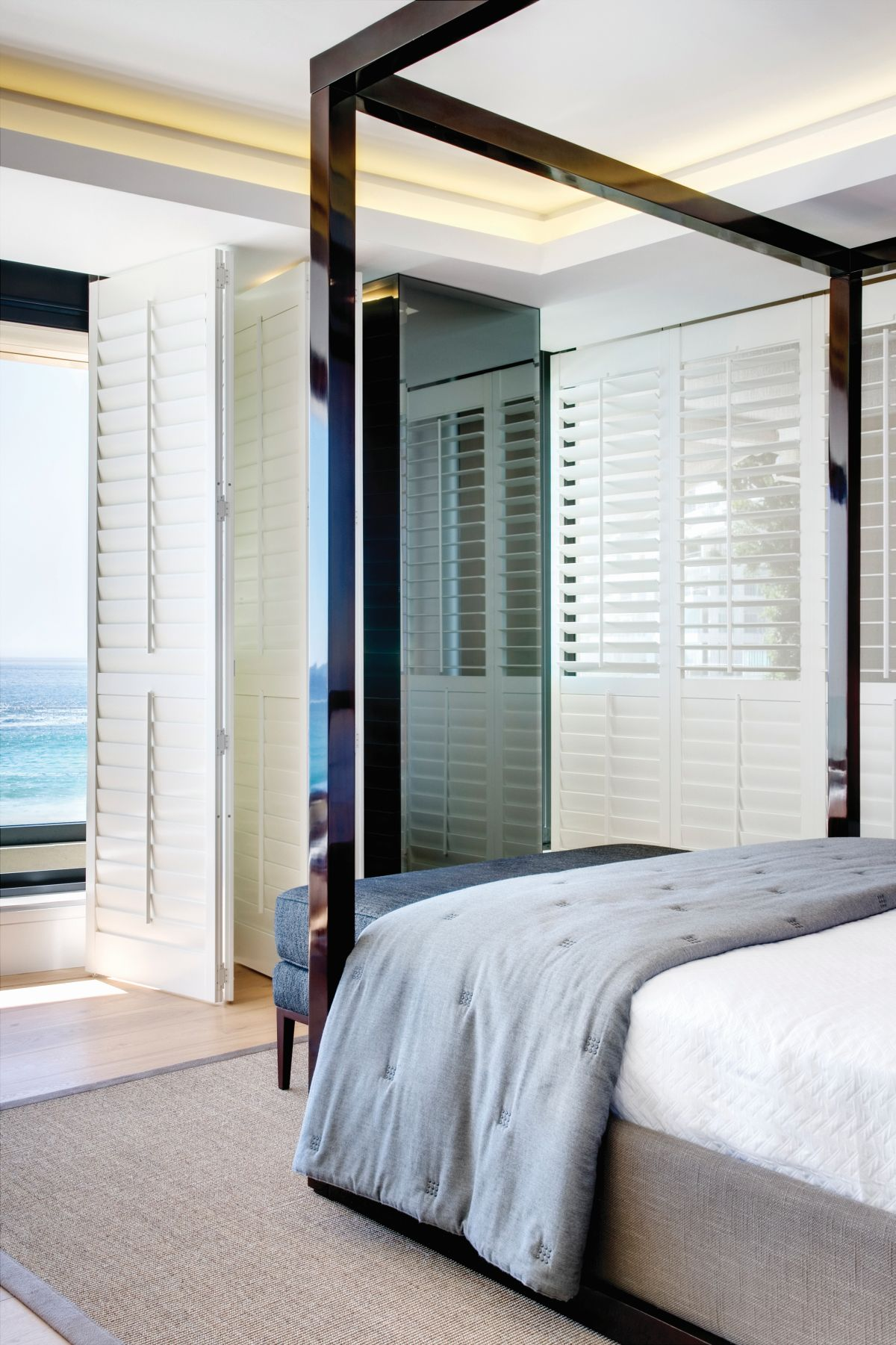 The wooden shutters giving the bedrooms a particularly casual look, in tone with the breezy ocean views