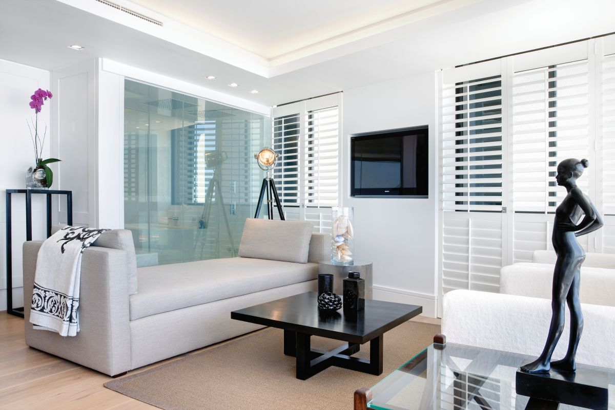 Dark accent pieces and black details highlight the decor and contrast with the white walls and ceilings