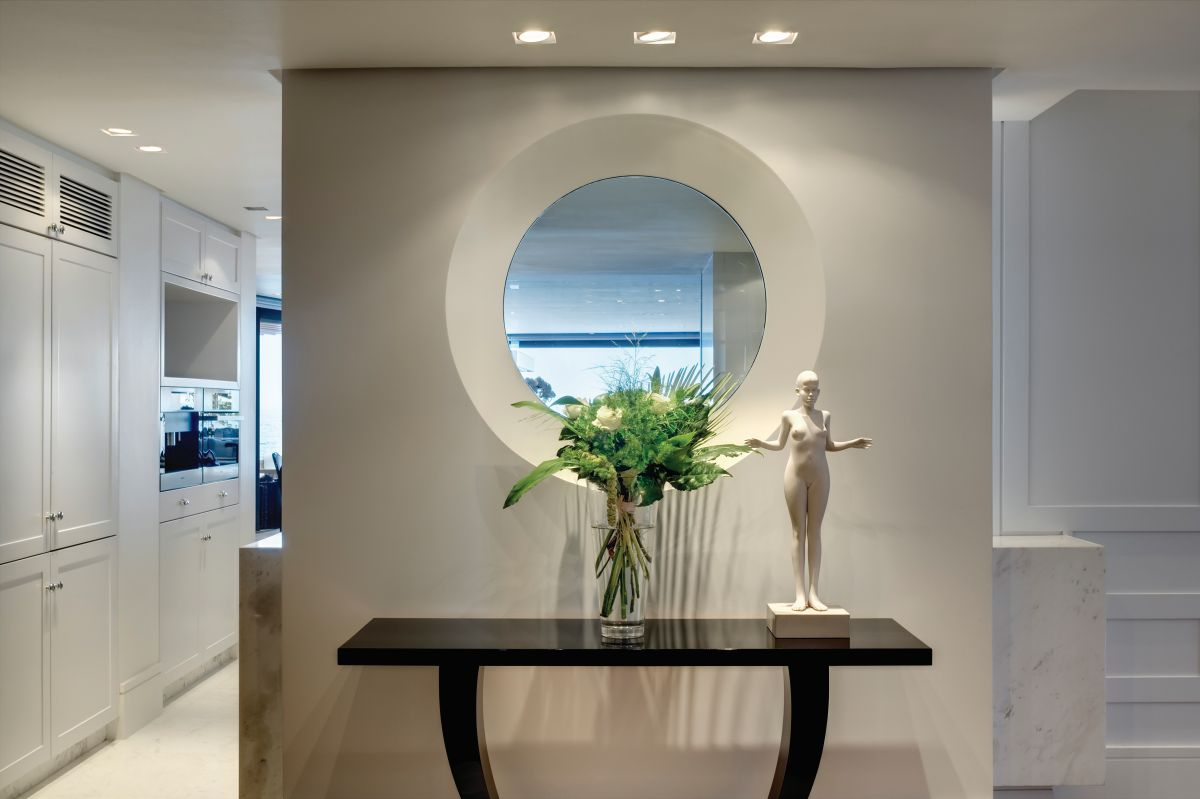 A stylish console table complemented by a small decorative statue and accent lighting adds a dramatic twist to the decor