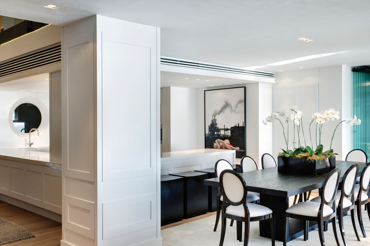 The dining area features a simple wood table framed by eight chic and timeless chairs with matching frames