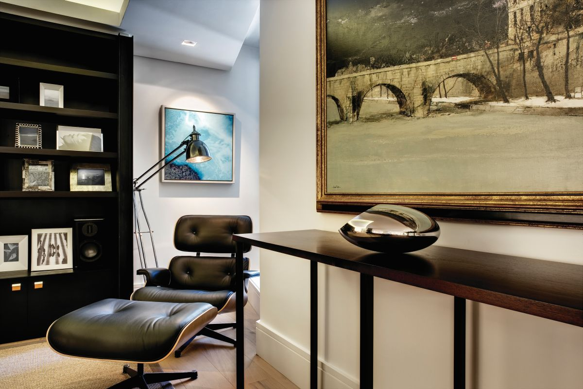 A timeless lounge chair with a matching ottoman and a floor lamp stand in the corner, creating the perfect reading nook