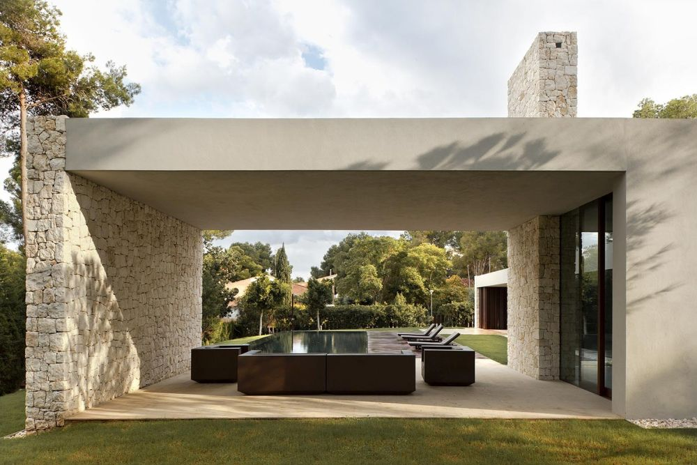 The living area's ceiling seamlessly extends outdoors, covering an open lounge area by the pool