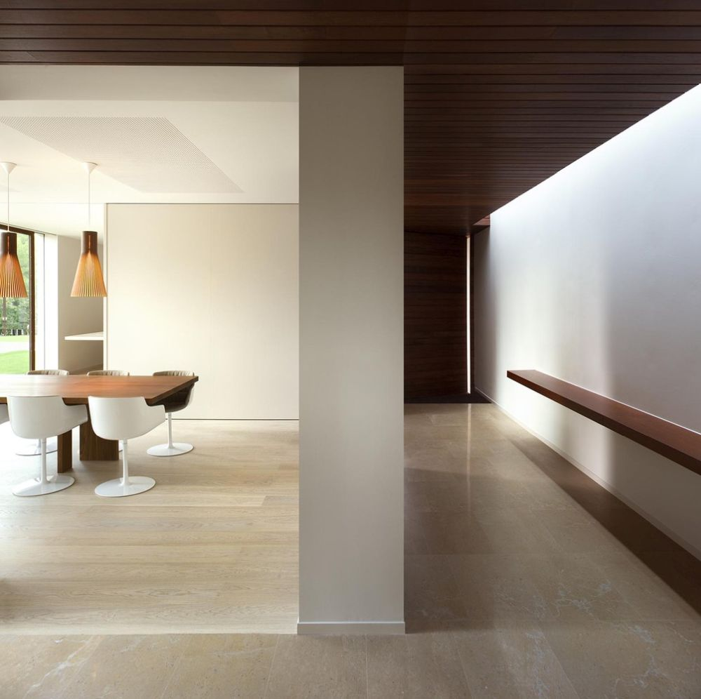 The entrance leads into a foyer with glazed partitions which connect the different areas of the house