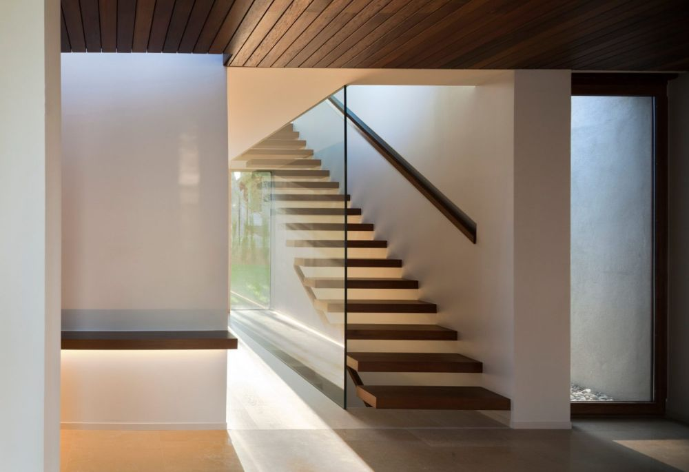 The staircase has floating treads and a transparent glass wall without a railing which allows the light to naturally flow through