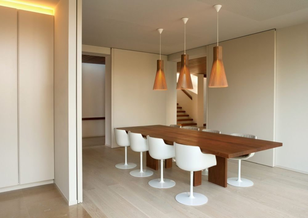 The dining area features light wooden flooring, a simple table, white pedestal chairs and three stylish pendant lamps