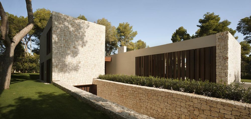 The solid stone walls allow the house to blend in with its natural surroundings while also offering it privacy