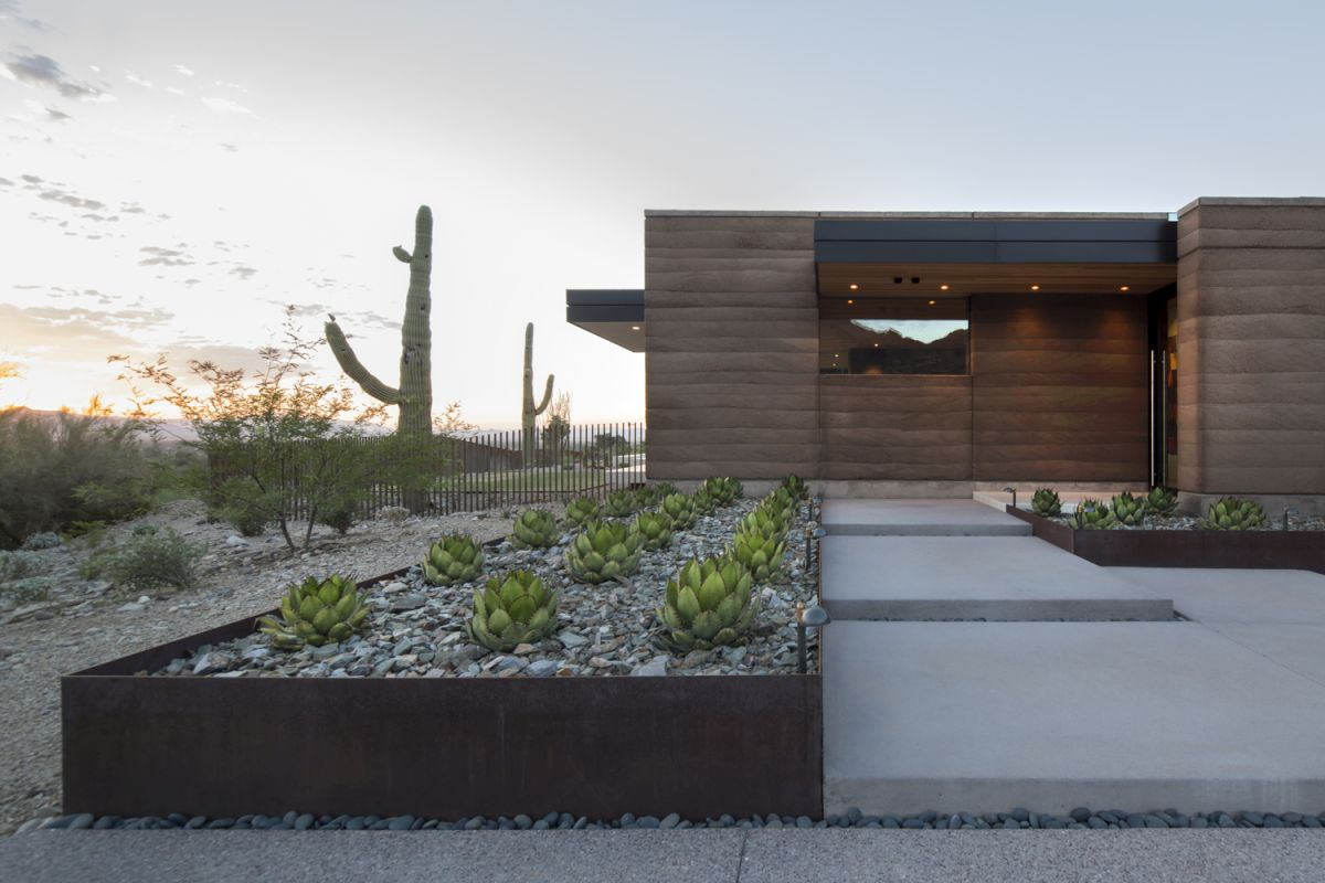 The wood-clad exterior allows the house to blend in with the surrounding landscape, mimicking the desert colors