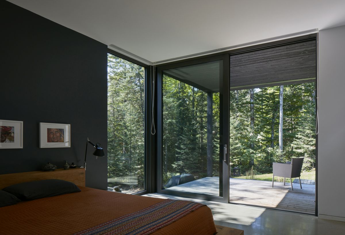 The master bedroom has access to a private porch as well and features full-height windows and sliding glass doors