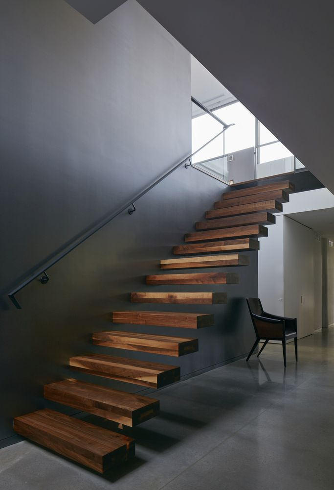 The wooden stairs contrast with the polished concrete flooring and the dark gray walls
