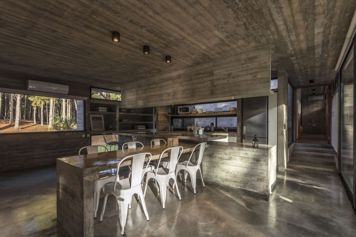 The kitchen is big and spacious, incorporating a dining table perpendicular to the island and parallel to the window
