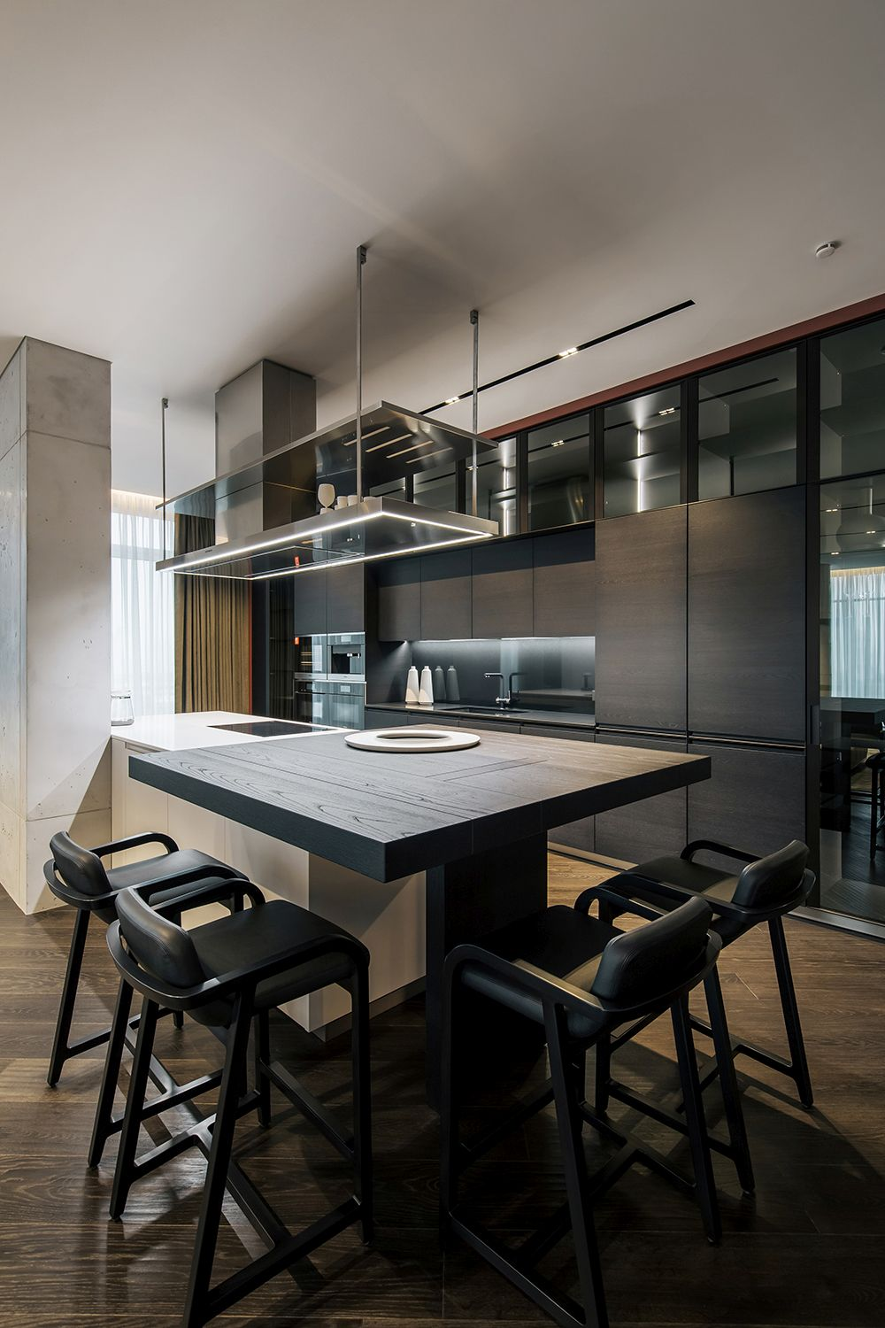 The kitchen features dark cabinetry and a two-tone island with a table/ bar extension