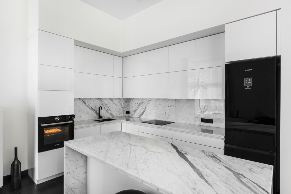 The kitchen is designed in black and white and has a stylish marble island with a waterfall countertop
