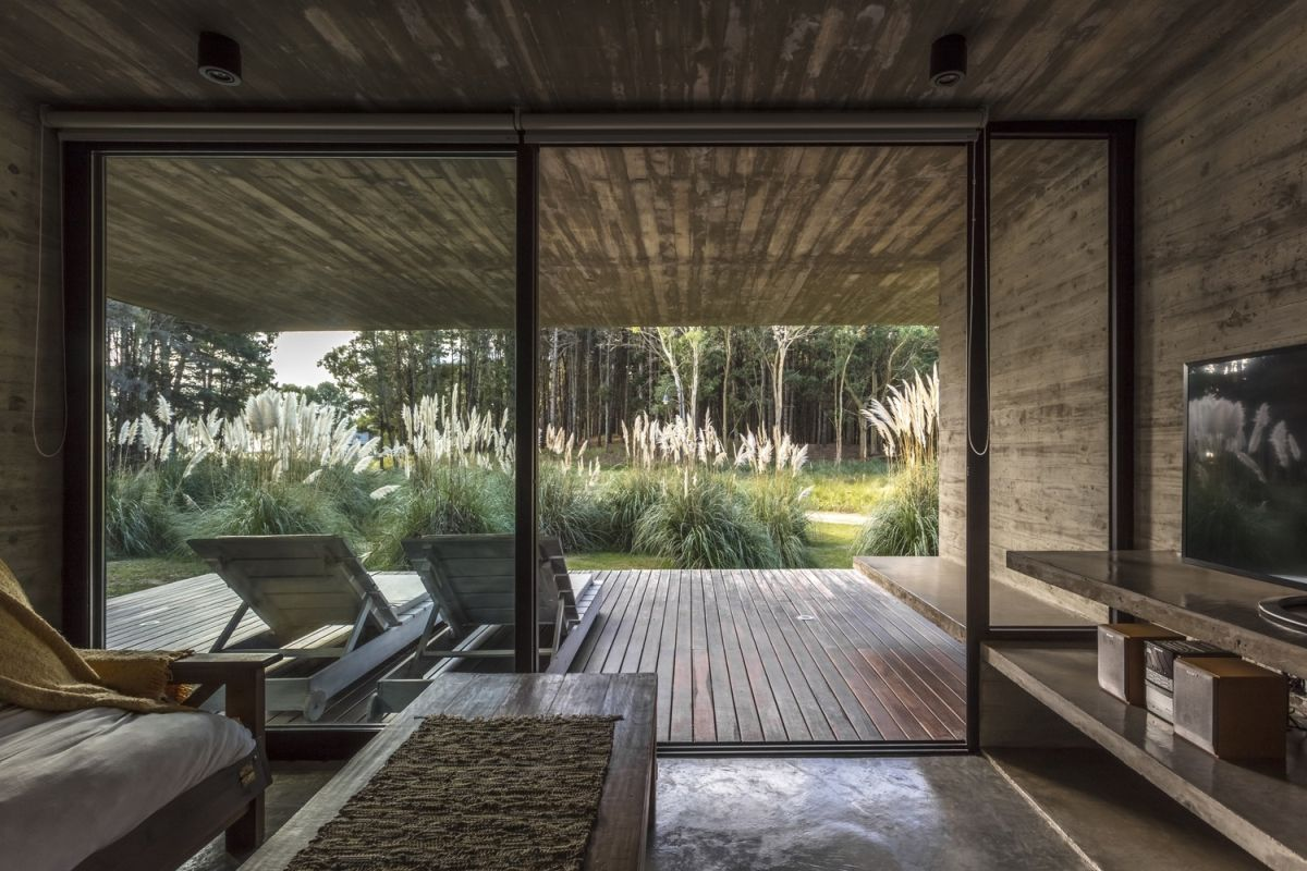 The living area seamlessly extends outdoors, featuring a sliding glass door to a large, covered deck