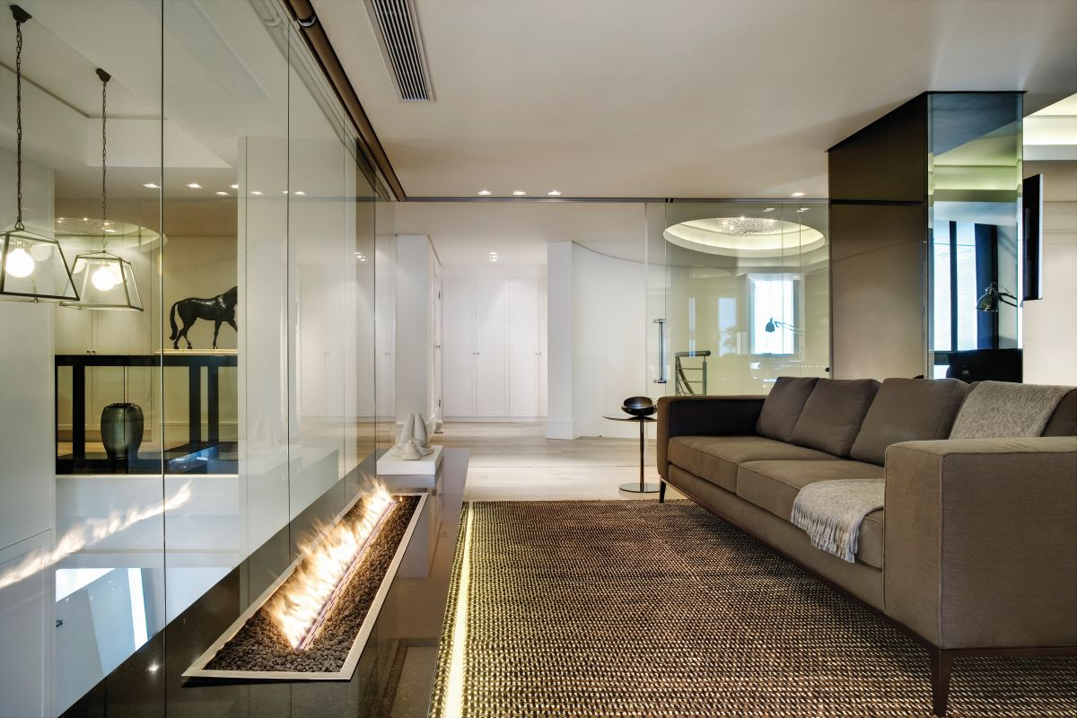 A secondary living area on the upper floor features an elegant sofa facing a contemporary fireplace