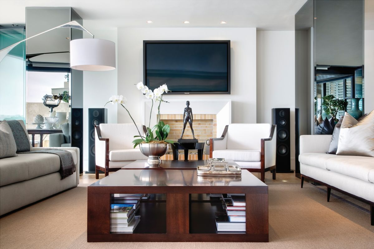 An oversized floor lamp complements the lounge area, extending over the sofa, towards the mahogany coffee table