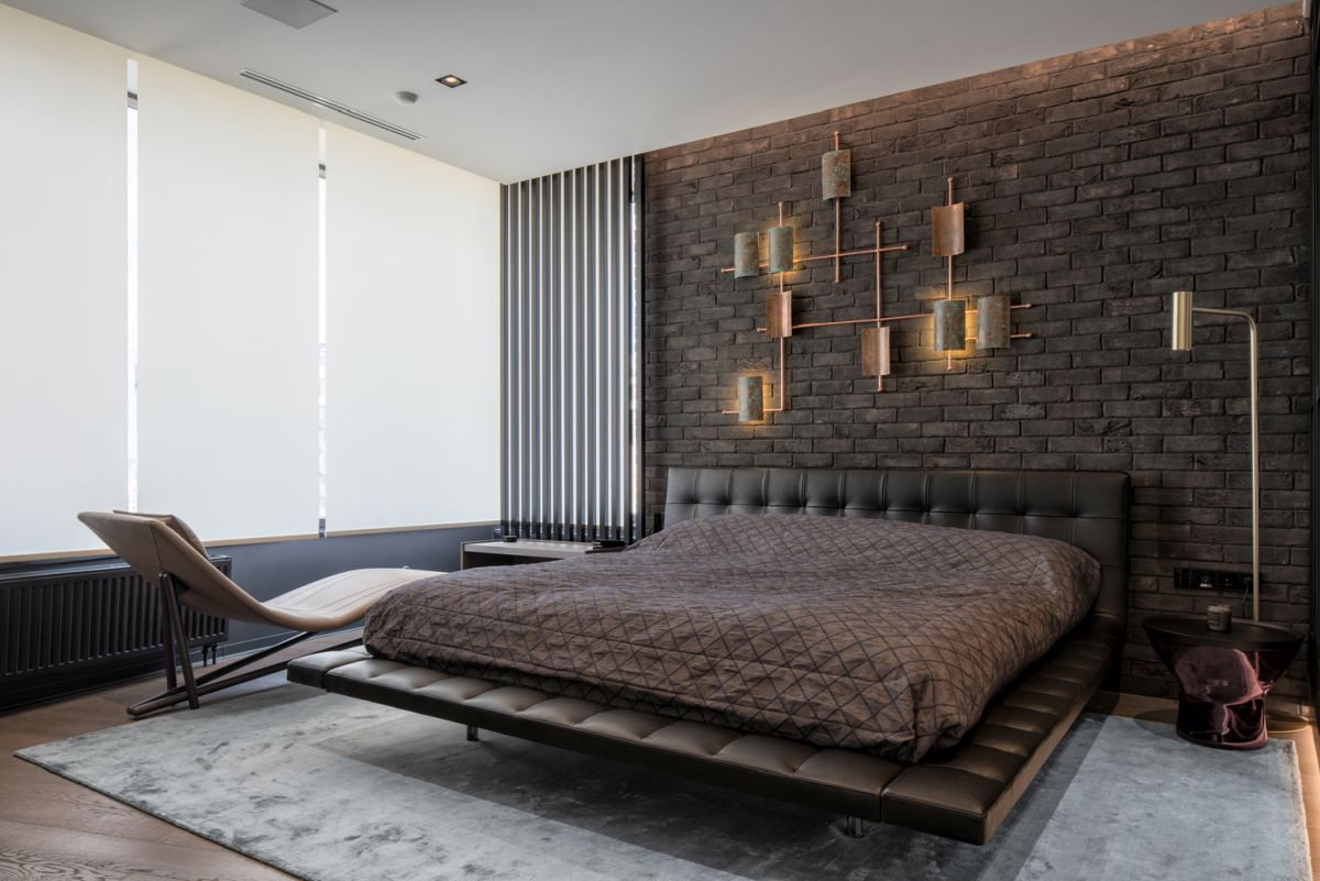 The textured brick wall gives the bedroom a warm and welcoming feel, balancing the dark chromatic palette