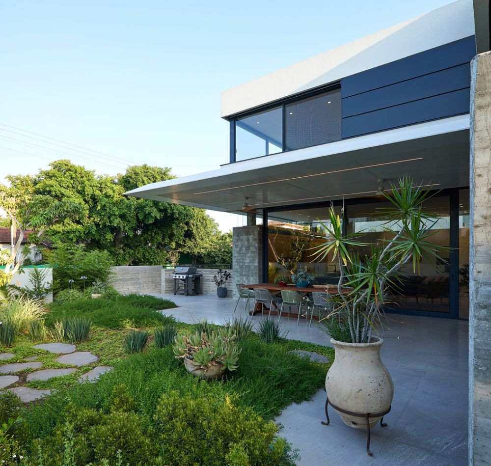 The house has an L-shaped floor plan with the inner lines facing the terrace and the garden