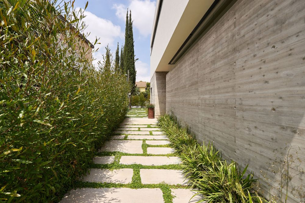 The outer lines of the L-shaped floor plan are facing the citrus trees and the concrete walls, for increased privacy