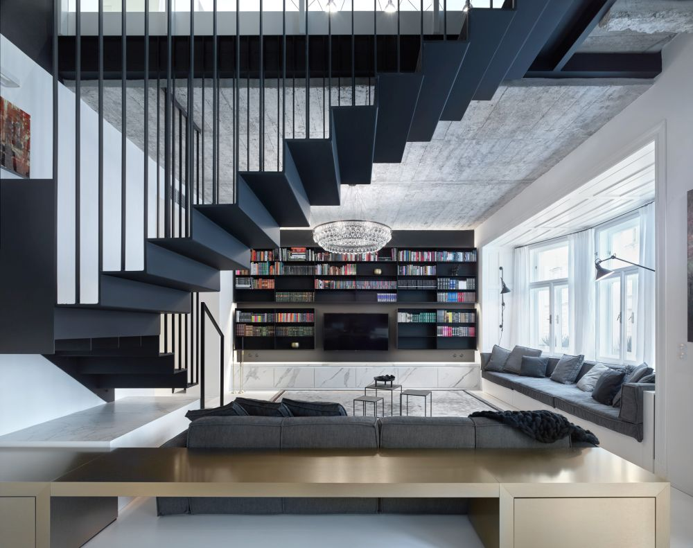 The suspended staircase acts as a focal point in the living area, drawing the eye up and emphasizing the high ceiling