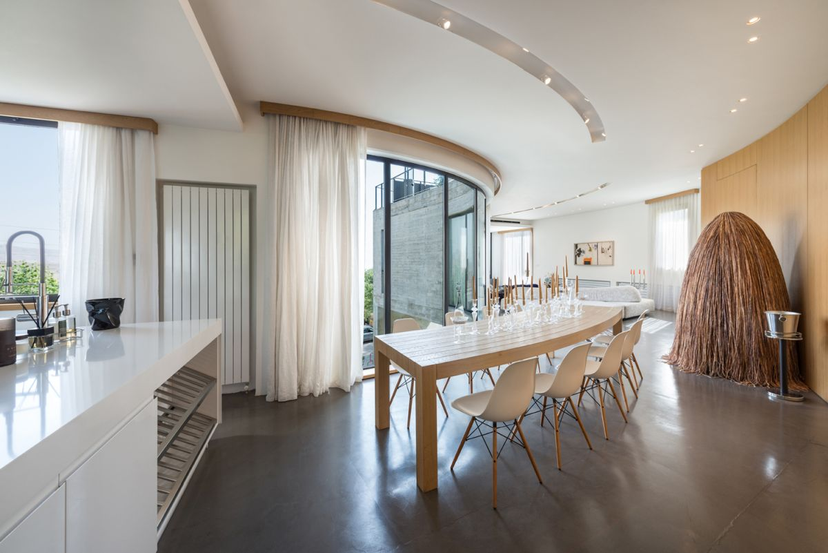 The dining room features a unique custom-built table with a curved and very stylish design