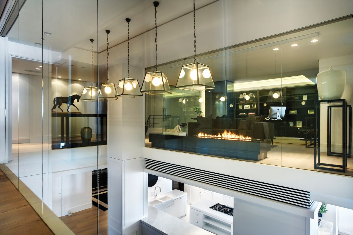 Glass walls and full-height windows allow the light to travel throughout the spaces, ensuring a sense of openness and transparency