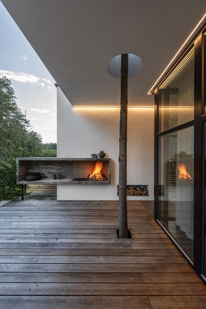 An open fireplace makes the deck feel extra cozy. There's a tree growing through the deck