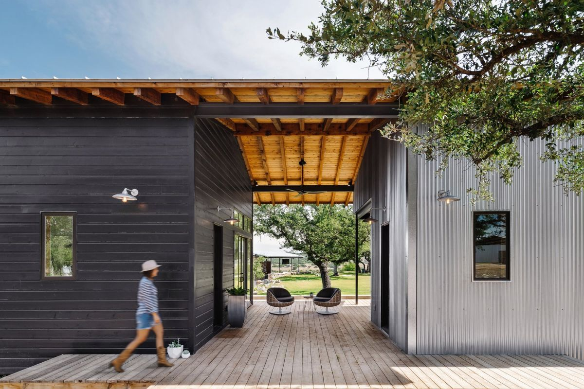 The updated. design of the ranch house features a metal roof and a black exterior which are complemented by light wood elements