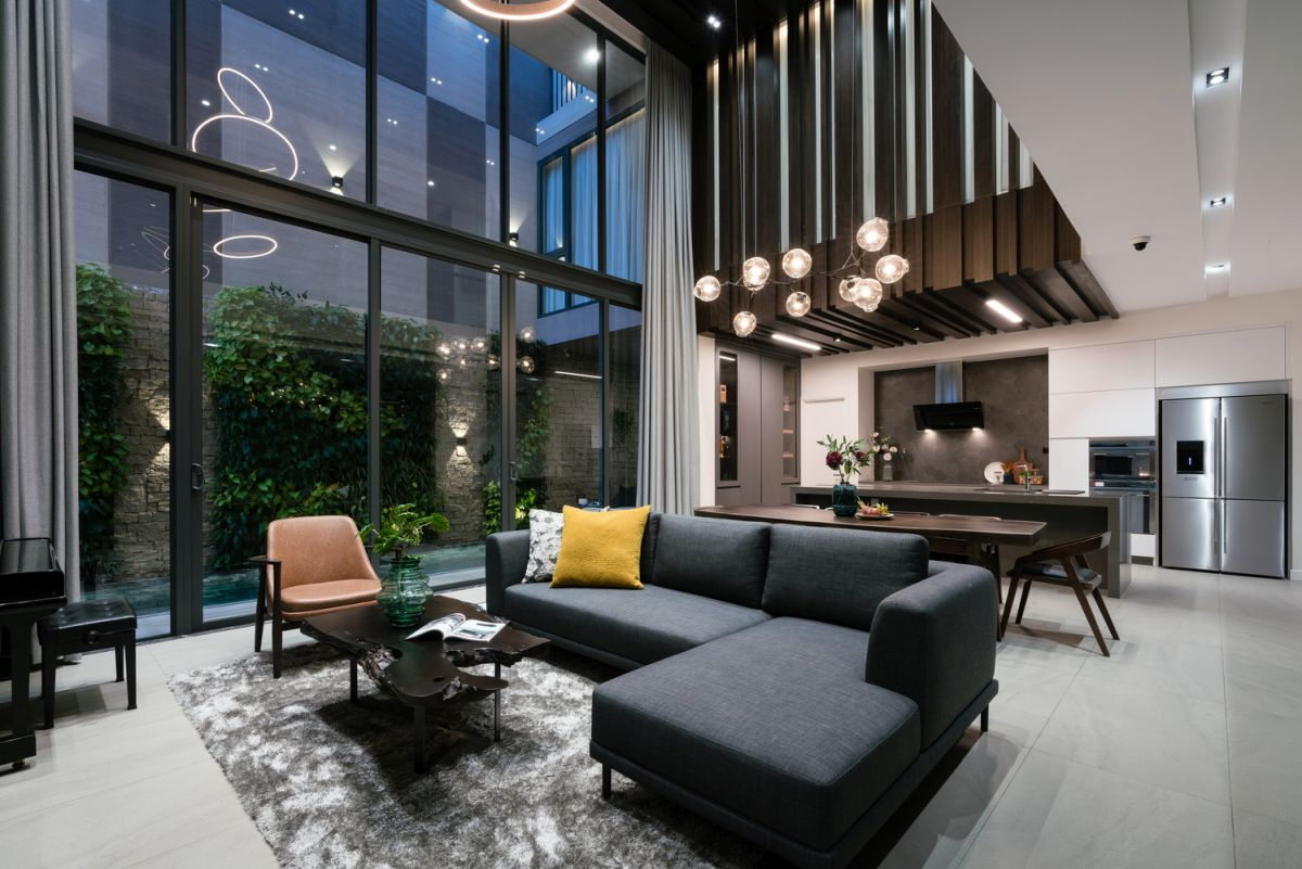 Chic and refined pendant lamps and chandeliers adorn the high ceiling in the living and dining areas