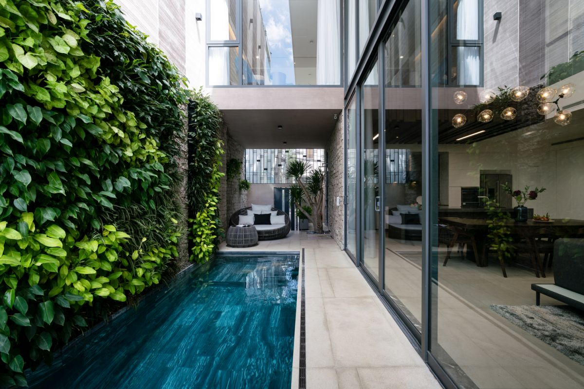 The living room and dining area have a direct view towards the pool and the green wall