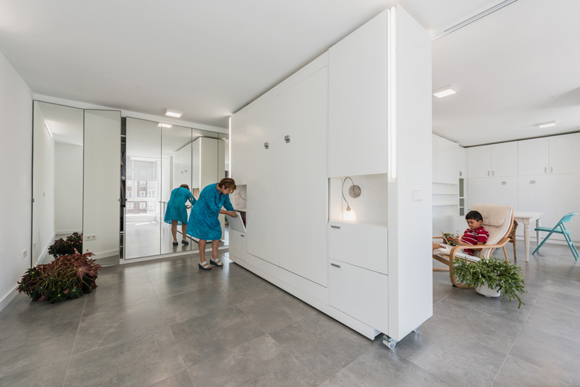 In addition to delineating the spaces, the moving wall is also packed with functionality and storage modules