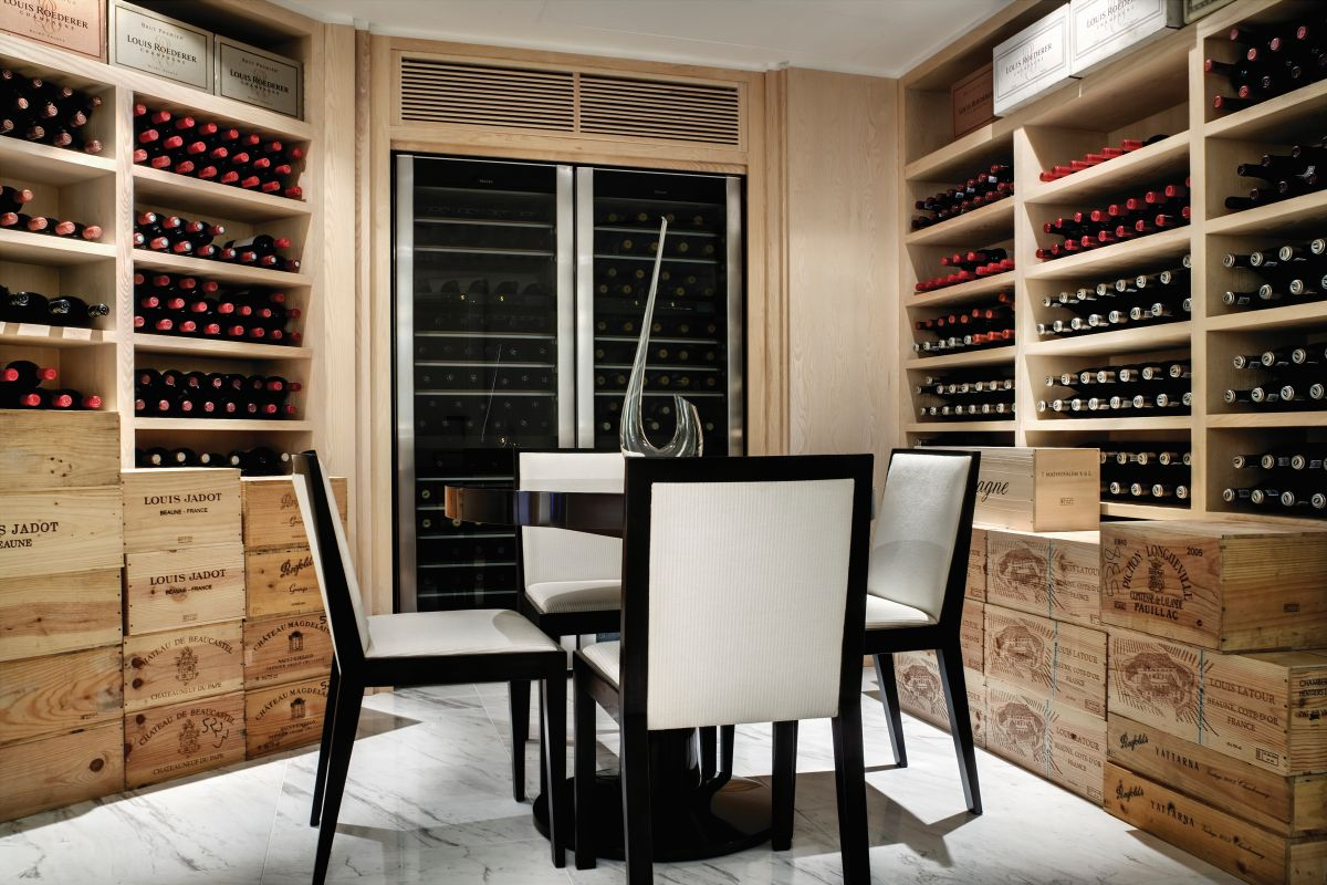 A private cellar features a series of wooden wall shelves and a built-in cooler and at the center of the space stands a small table with four chairs