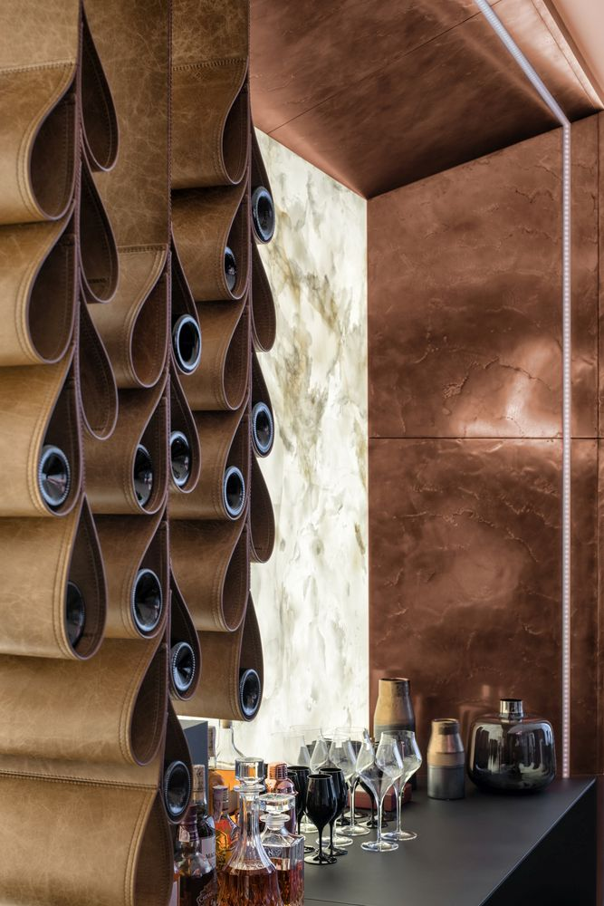 A stylish wine rack with leather pockets stands out against the backlit onyx panel