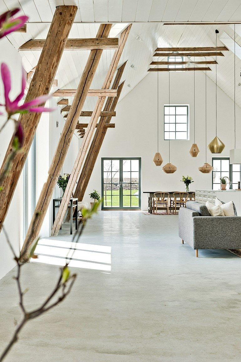 A series of low hanging pendant lamps are suspended from the high ceiling complementing