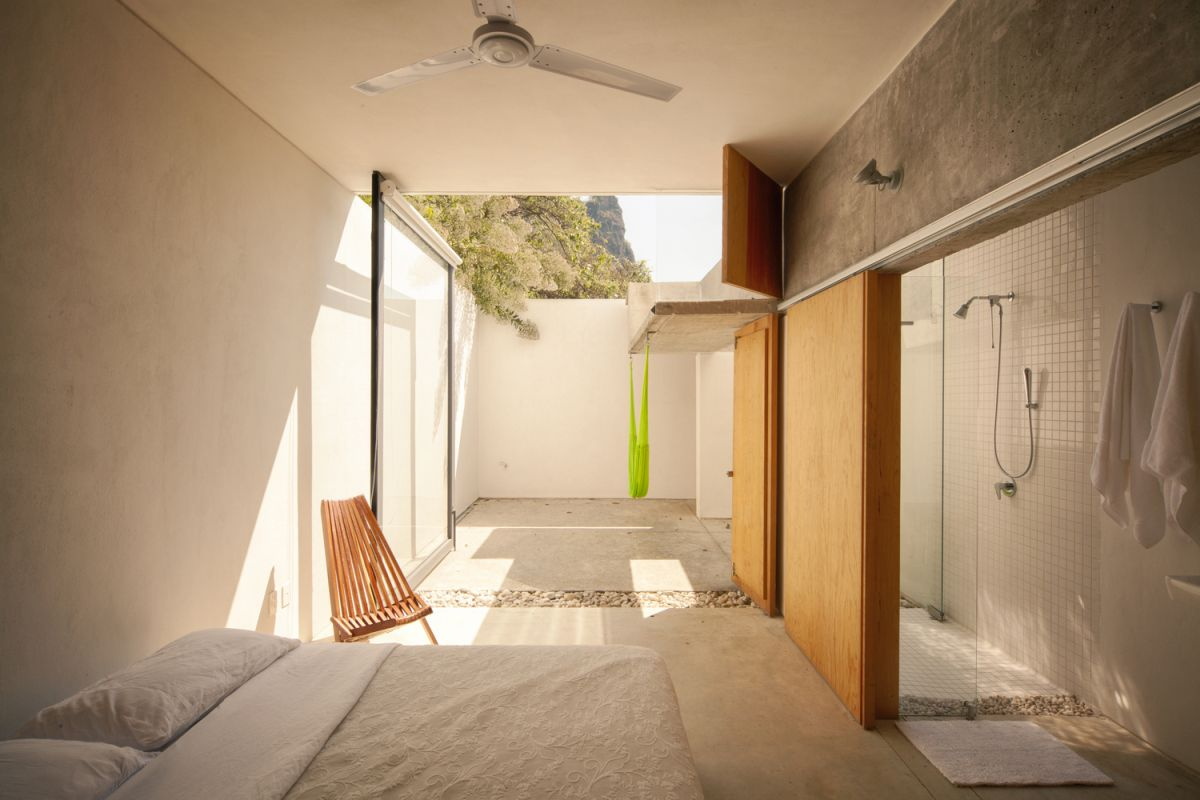 The bedroom opens onto an enclosed courtyard with an open roof and hammocks