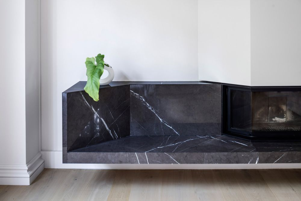 Dark marble was used to create this stylish fireplace nook which is great for storing firewood