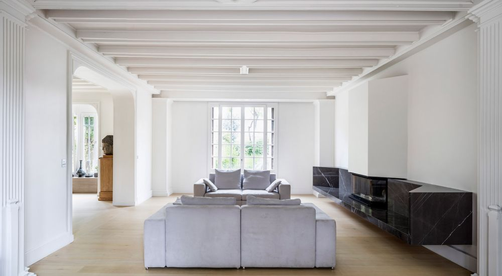In the living room, a pair of comfortable two-seater sofas form a cozy sitting area