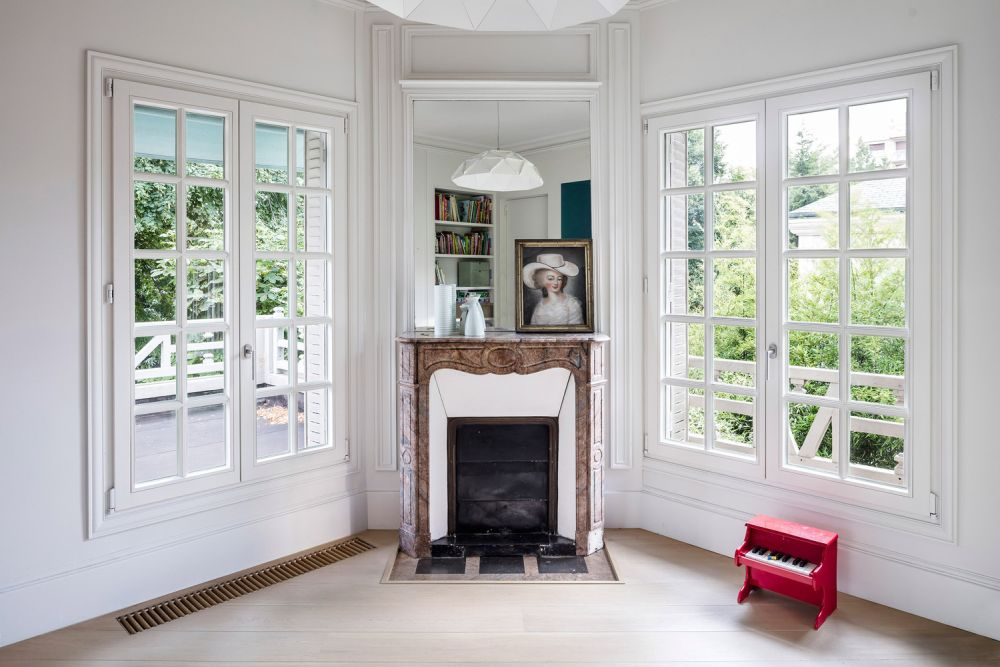 A corner fireplace adds charm to this room, maintaining a symmetrical look