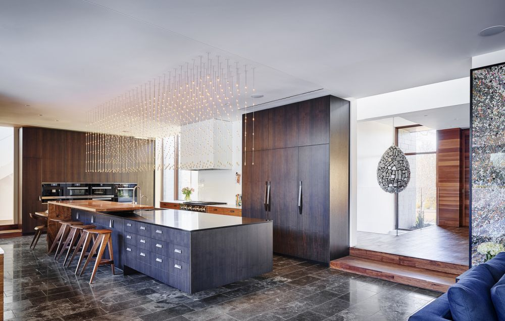 The high-end kitchen features a large island with an exquisite light fixture hanging above it