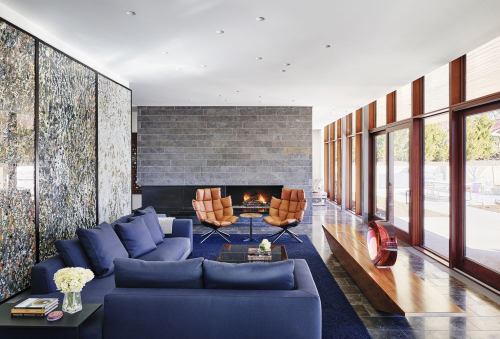 The living area is a cozy and welcoming space, with large windows and a comfortable sectional sofa in a color that matches the rug