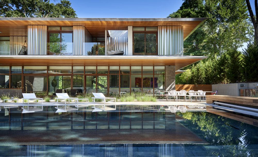 The glazed facade faces the backyard and a large swimming pool, bringing the outdoors in