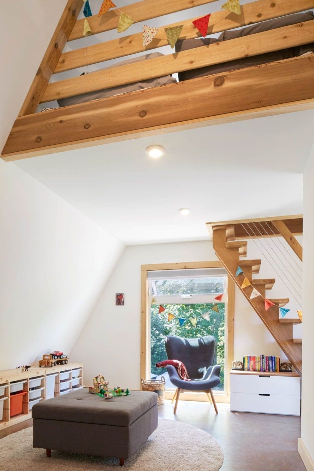 The upstairs space overlooks the living room below and the two floors are connected by a wood staircase