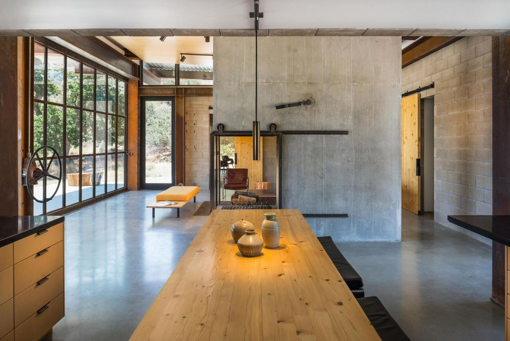A glass-enclosed fireplace is embedded into the concrete divider between the lounge space and the dining area