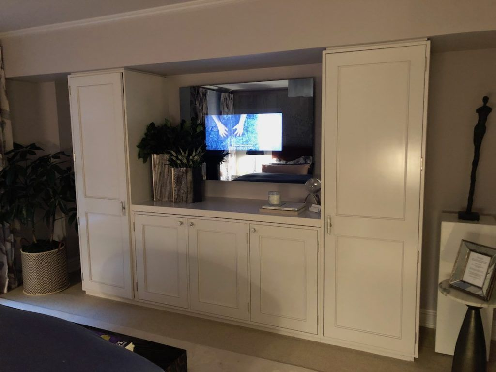 Across from the bed, the built-ins flank a television that is built into the mirror.